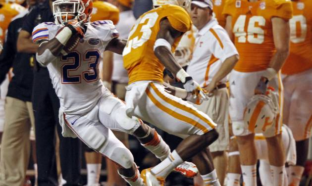Florida running back Mike Gillislee (23) runs for yardage as he's defended by Tennessee defensive back Prentiss Waggner (23) in the third quarter of an NCAA college football game on Saturday, Sept. 15, 2012, in Knoxville, Tenn. Florida won 37-20. (AP Photo/Wade Payne)