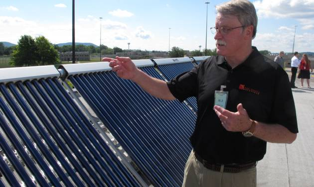 Charlie Slavik, marketing and sales vice president for Indianapolis-based Solar America Solutions, discusses the workings of a solar panel array atop a prison building at Ross Correctional Institution on Wednesday, July 16, 2014, in Chillicothe, Ohio. Slavik says the panels are about both being green and giving inmates trained to install and maintain them a second chance. (AP Photo/Andrew Welsh-Huggins)