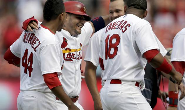 St. Louis Cardinals' Yadier Molina, second from left, celebrates with teammates Carlos Martinez (44), Oscar Taveras (18) and Jhonny Peralta after scoring a baseball game-winning run on a single by Peter Bourjos during the ninth inning against the Pittsburgh Pirates, Wednesday, Sept. 3, 2014, in St. Louis. The Cardinals won 1-0. (AP Photo/Jeff Roberson)