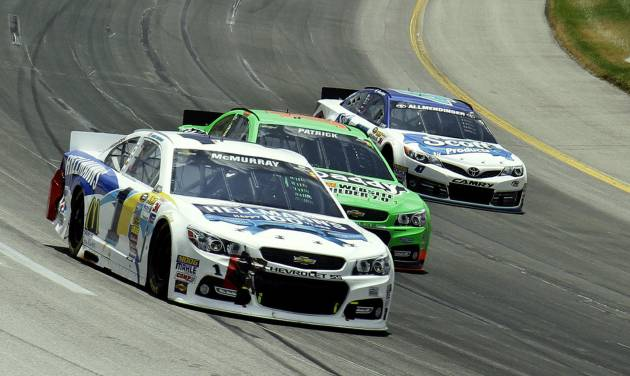 Jamie McMurray (1) goes outside to pass Danica Patrick (10) and A.J. Allmendinger (47) in Turn 4 early in the NASCAR Sprint Cup auto race at Kentucky Speedway in Sparta, Ky., Sunday, June 30, 2013. McMurray finished second behind Matt Kenseth in the race.  (AP Photo/Garry Jones)
