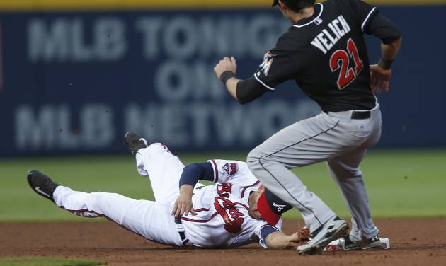 Atlanta Braves shortstop Andrelton Simmons (19) forces Miami Marlins' Christian Yelich (21) out at second base on a Jordany Valdespin (1) ground ball in the fourth inning of a baseball game  in Atlanta, Monday, July 21, 2014. (AP Photo/John Bazemore)