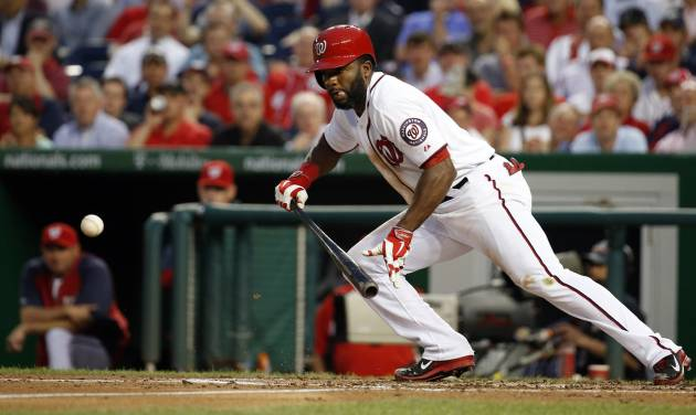 Washington Nationals' Denard Span bunt during the third inning of a baseball game against the Cincinnati Reds at Nationals Park on Tuesday, May 20, 2014, in Washington. Span reached first and made it all the way to third on an error on the play. (AP Photo/Alex Brandon)