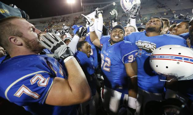 Tulsa offensive tackle Jared Grigg (72) leads his teammates in celebrating a 31-17 win over Iowa State in the Liberty Bowl NCAA college football game in Memphis, Tenn., Monday, Dec. 31, 2012. (AP Photo/Rogelio V. Solis)