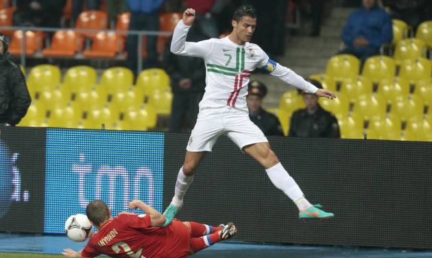 Portugal's Cristiano Ronaldo jumps over Russia's Aleksandr Anyukov, bottom, in their World Cup 2014 Group F qualification match at Luzhniki stadium in Moscow, Russia, on Friday, Oct. 12, 2012. (AP Photo/Mikhail Metzel)