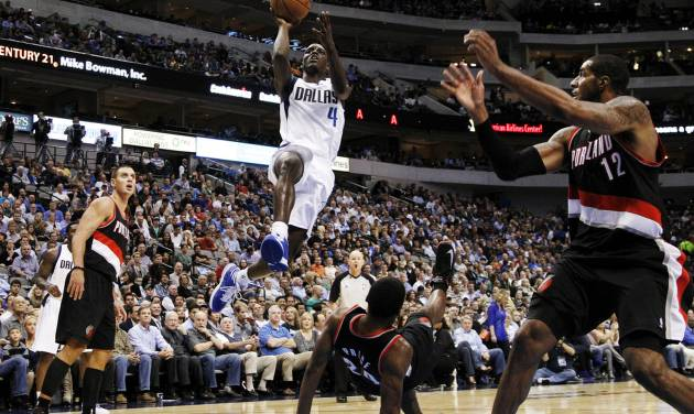 Dallas Mavericks' Darren Collison (4) leaps over a falling Portland Trail Blazers' Ronnie Price (24) to shoot as Sasha Pavlovic, left, and LaMarcus Aldridge (12) watch in the second half of an NBA basketball game, Monday, Nov. 5, 2012, in Dallas. The Mavericks won 114-91. (AP Photo/Tony Gutierrez)