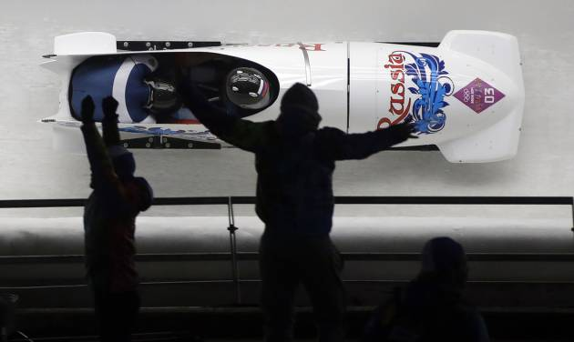 Fans jump and cheer as the team from Russia RUS-1, piloted by Alexander Zubkov and brakeman Alexey Voevoda, speeds down the track during the men's two-man bobsled competition at the 2014 Winter Olympics, Sunday, Feb. 16, 2014, in Krasnaya Polyana, Russia. (AP Photo/Dita Alangkara)