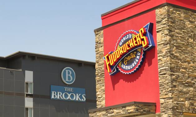 In this July 3, 2014 photo, the Brooks Hotel and a Fuddruckers restaurant are seen in Williston, N.D. North Dakota's oil boom has not escaped the eyes of foreign investors. Two foreign investment firms are trying to bring two large-scale mixed-use developments worth a total of $800 million to the state's oil patch. (AP Photo/Josh Wood)