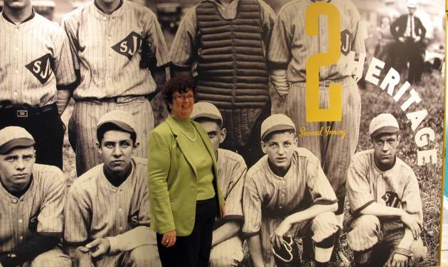 In this Wednesday, April 24, 2013 photo, Karen Stotz Myers, the daughter of Little League Baseball founder Carl Stotz, poses in front of a picture at a new exhibit at the Little League museum in South Williamsport, Pa. Kneeling on the ground in the image, to Stotz Myers' right, is her father in a picture taken when he was a boy playing for his school team. (AP Photo/Genaro C. Armas)