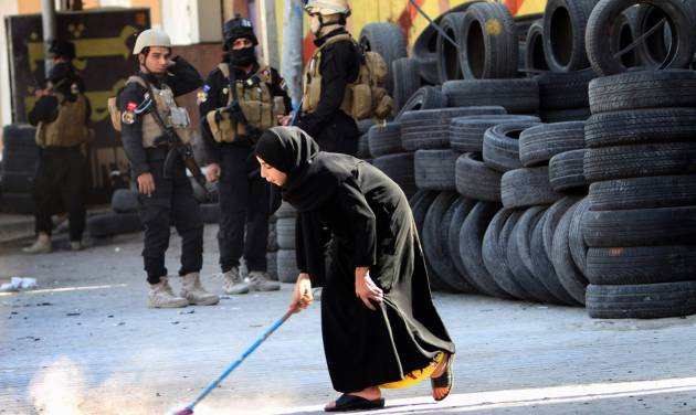 A young woman sweeps debris from the site of a car bomb attack in Basra, 340 miles (550 kilometers) southeast of Baghdad, Iraq, Sunday, Oct. 13, 2013. A string of bombings in mostly Shiite-majority cities across Iraq on Sunday killed and wounded dozens of people, officials said, a grim reminder of the government's failure to stem the uptick in violence that is feeding sectarian tensions in the country.(AP Photo/Nabil al-Jurani)