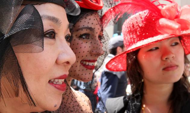 Marjorie Lee Woo, left, Sabrina Mashburn, center, and Ashley Woo, Marjorie's daughter, pose for photographers as they take part in the Easter Parade along New York's Fifth Avenue Sunday April 24, 2011. Marjorie Lee Woo made the hats. (AP Photo/Tina Fineberg)