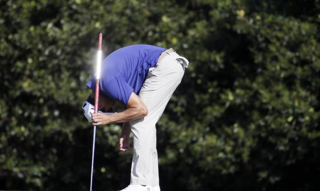 Adam Scott, of Australia, reacts after missing a birdie putt on the 11th hole during the third round of the Masters golf tournament Saturday, April 12, 2014, in Augusta, Ga. (AP Photo/Darron Cummings)