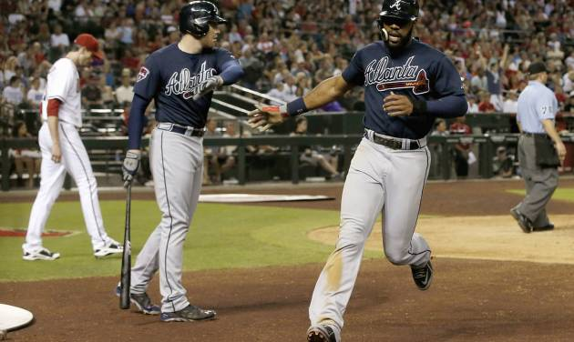 Atlanta Braves' Jason Heyward, right, slaps hands with teammate Freddie Freeman, middle, after Heyward scored a run as Arizona Diamondbacks pitcher Brandon McCarthy, left, walks behind home plate during the seventh inning of a baseball game on Friday, June 6, 2014, in Phoenix. (AP Photo/Ross D. Franklin)