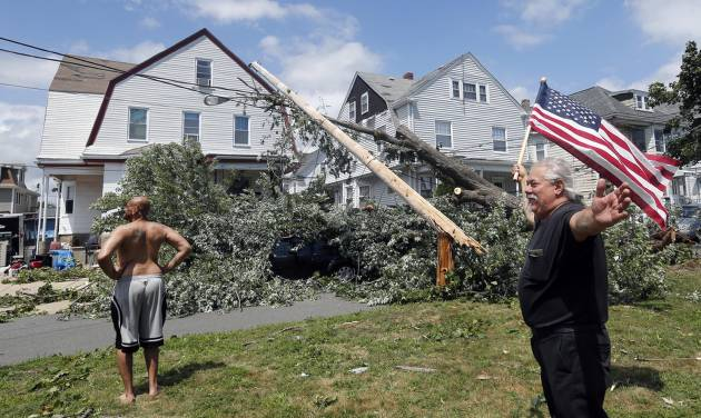 Homeowner Lenny DiBartolomeo, right, waves a flag as he and his tenant Wayne Devaughn, left, observe damage to their house in Revere, Mass., Monday, July 28, 2014, after a tornado touched down. Both men said they were grateful that they knew of no injuries. (AP Photo/Elise Amendola)