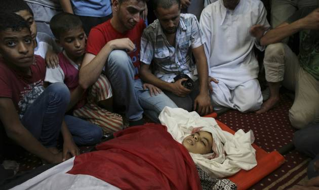 Palestinian relatives mourn over the body of Noor Alnajedy, 10,  who was killed during an Israeli air strike on a building near his family house, at the main mosque during his funeral in Rafah refugee camp, southern Gaza Strip, Friday July 11, 2014. Israel launched the Gaza offensive to stop incessant rocket fire that erupted after three Israeli teenagers were kidnapped and killed in the West Bank and a Palestinian teenager was abducted and burned to death in an apparent reprisal attack. The military says it has hit more than 1,100 targets already, mostly what it identified as rocket-launching sites, bombarding the territory on average every five minutes. (AP Photo/Eyad Baba)