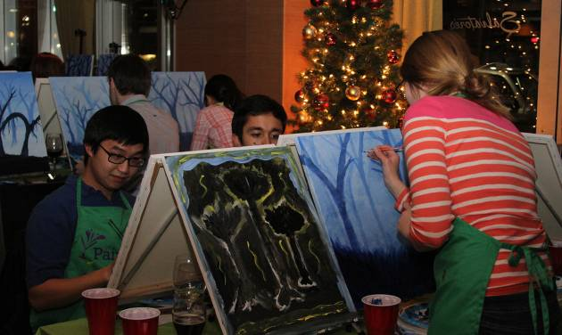 In this Dec. 4, 2013, photo, provided by Lattice Engines, Lattice Engines's Boston office participates in Paint Nite, in Boston.  Paint Nite is a service event that gives painting lessons at bars and restaurants. About sixty-five people attended.  (AP Photo/ Lattice Engines)