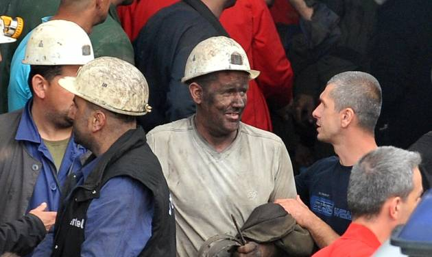 Coal miners carry out a fellow miner, center, who was injured while he was trapped in coal mine Raspotocje in Zenica,70 kms north of Sarajevo , Bosnia, on Friday, Sept.5, 2014 . Rescuers on Friday were pulling out some of the 34 miners who had been trapped deep inside a coal mine that collapsed in central Bosnia. Tired, their faces smeared with coal dust, the men came out of the Zenica mine one by one, after spending the night more than 500 meters (1,600 feet) below the ground. (AP Photo/Amel Emric)