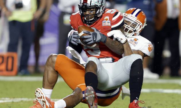 Ohio State quarterback Braxton Miller is brought down by Clemson defensive end Vic Beasley during the first half of the Orange Bowl NCAA college football game, Friday, Jan. 3, 2014, in Miami Gardens, Fla. (AP Photo/Lynne Sladky)