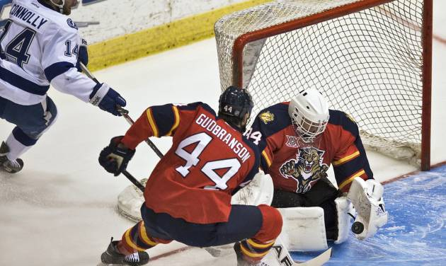 Florida Panthers defender Erik Gudbranson (44) watches as goalie Tim Thomas, right, stops a shot from Tampa Bay Lightning' Brett Connolly (14) during the first period of an NHL preseason hockey game Thursday, Sept. 26, 2013, in Estero, Fla. (AP Photo/Steve Nesius)