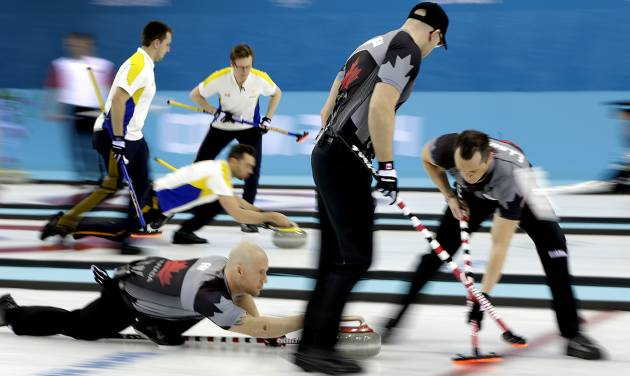 Canada's Ryan Fry delivers the rock while E.J. Harnden, right, and Ryan Harnden, center, sweeps the ice during the men's curling competition against Denmark at the 2014 Winter Olympics, Thursday, Feb. 13, 2014, in Sochi, Russia. (AP Photo/Wong Maye-E)