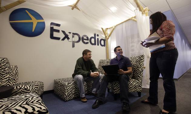 In this Tuesday, Jan. 15, 2013, photo, Expedia analytics team workers Mike Brown, left, Saurin Pandya and Prashanti Tata chat in an alcove set up for employees  in Bellevue, Wash. Soaring hotel bookings pushed revenue higher at Expedia Inc., but the online travel agency's fourth-quarter profit fell 90 percent because of money it set aside to appeal a tax dispute in Hawaii. (AP Photo/Elaine Thompson)