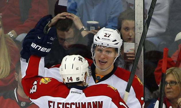 Florida Panthers' Nick Bjugstad (27) celebrates his goal with teammate Tomas Fleischmann (14), of the Czech Republic, against the New Jersey Devils during the second period of an NHL hockey game in Newark, N.J., Saturday, Jan. 11, 2014. (AP Photo/Rich Schultz)