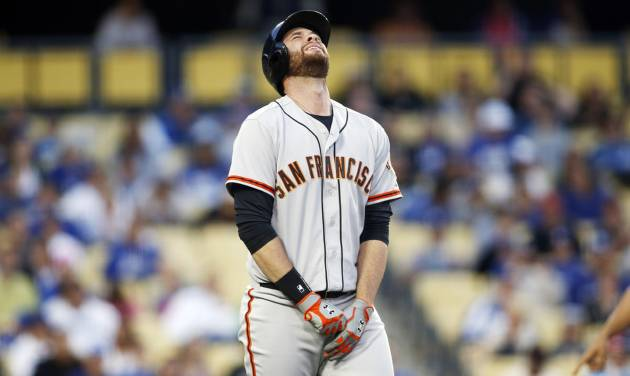 San Francisco Giants' Brandon Belt reacts after being hit by a pitch on his left hand against the Los Angeles Dodgers during the second inning of a baseball game, Friday, May 9, 2014, in Los Angeles. (AP Photo/Danny Moloshok)