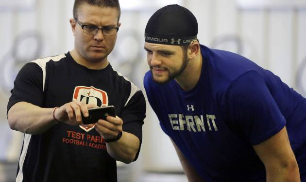 FILE - In this Friday, Feb. 14, 2014 file photo, Coach Kevin Dunn, left, goes over some techniques for the 40-yard-dash, between runs, with Gallaudet defensive lineman Adham Talaat, right, at his TEST Sports Clubs in Martinsville, N.J. Talaat has overcome being deaf to reach the doorstep of the NFL. After starring at Gallaudet University, working out at Test Parisi Football Academy and posted impressive numbers at his Pro Day, the talented defensive end is hopeful he'll get a call when the NFL draft kicks off next week. (AP Photo/Mel Evans,file)