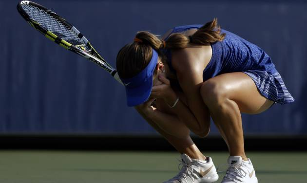 Catherine Bellis, of the United States, drops to her knees after defeating Dominika Cibulkova, of Slovakia, during the first round of the 2014 U.S. Open tennis tournament, Tuesday, Aug. 26, 2014, in New York. (AP Photo/Darron Cummings)