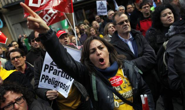 Protestors shout slogans as they carry a  banner reading 'Popular Party, dangerous party' during a protest against a measure raising Court fees in Madrid, Saturday, Jan. 19, 2013. Spain has sold euros 4.5 billion ($5.97 billion) in a medium- and long-term bond sale that saw interest rates dropping as market fears ease over whether the country will need outside help to manage its finances. (AP Photo/Andres Kudacki)
