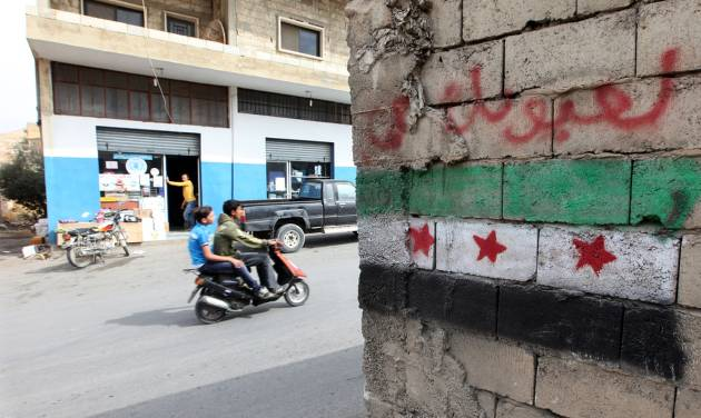 In this Tuesday, Oct. 2, 2012 photo, a Syrian revolution flag painted on a wall in Arsal, a Sunni Muslim town eastern Lebanon near the Syrian border, has become a safe haven for war-weary Syrian rebels and hundreds of refugee families. Many in Arsal support the rebels, but the town's stand is risking heightened tensions with its Shiite Muslim neighbors in an area controlled by Hezbollah, a militia that backs the Syrian regime. Deepening sectarian rifts are one of the ways in which Syria's 18-month-old conflict is destabilizing an already volatile region. (AP Photo/Bilal Hussein)