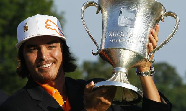 Rickie Fowler holds the trophy after winning the Wells Fargo Championship golf tournament at Quail Hollow Club in Charlotte, N.C., Sunday, May 6, 2012. (AP Photo/Gerry Broome)