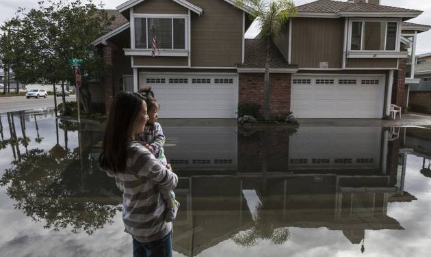 Newly moved in resident Juliana Chen steps out of her garage with her daughter into the overflowed street onto Pacific Coast Highway in the Sunset Beach area of Huntington Beach, Calif., Thursday, Dec. 13, 2012. Astronomical high tides have caused minor street flooding in some low-lying areas along the Southern California coast. (AP Photo/Damian Dovarganes)