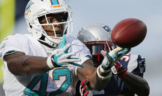 New England Patriots free safety Devin McCourty, right, breaks up a pass intended for Miami Dolphins tight end Charles Clay (42) in the first half of an NFL football game on Sunday, Oct. 27, 2013, in Foxborough, Mass. (AP Photo/Michael Dwyer)