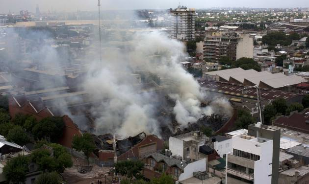 Smoke rises from the Iron Mountain warehouse in Buenos Aires, Argentina, Wednesday, Feb. 5, 2014. Nine first-responders were killed in the fire that destroyed an archive of bank documents, according to authorities. (AP Photo/Rodrigo Abd)