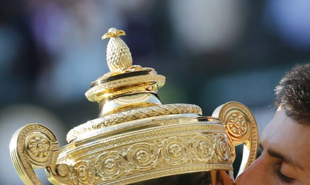Novak Djokovic of Serbia kisses the trophy after defeating Roger Federer of Switzerland in the men's singles final match at the All England Lawn Tennis Championships in Wimbledon, London, Sunday July 6, 2014.(AP Photo/Ben Curtis)