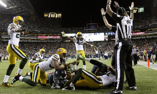 Officials signal after Seattle Seahawks wide receiver Golden Tate pulled in a last-second pass from quarterback Russell Wilson to defeat the Green Bay Packers 14-12 in an NFL football game, Monday, Sept. 24, 2012, in Seattle. The touchdown call stood after review. (AP Photo/The Seattle Times, John Lok) MAGS OUT; NO SALES; SEATTLEPI.COM OUT; MANDATORY CREDIT; USA TODAY OUT; TV OUT