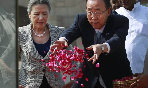 U.N. Secretary-General Ban Ki-moon, right, throws flowers as wife Yoo Soon-taek looks on as they pay respects at Rajghat, the memorial to the late Mahatma Gandhi in New Delhi, India, Friday, April 27, 2012. Ban is on a three day official visit to India. (AP Photo/Kevin Frayer)