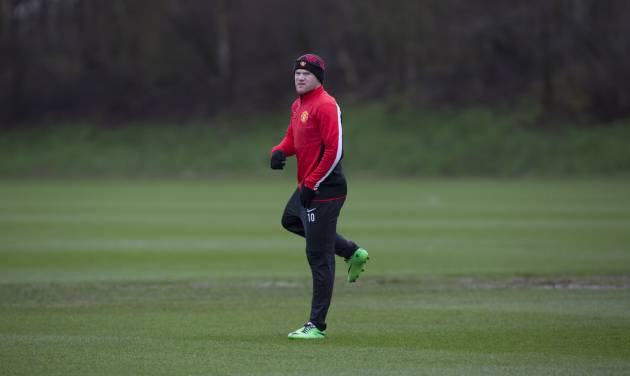 Manchester United's Wayne Rooney trains with teammates at Carrington training ground in Manchester, Monday, Feb. 24, 2014. Manchester United will play Olympiakos in a Champions League first knockout round on Tuesday. (AP Photo/Jon Super)