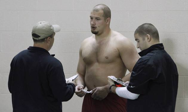 Offensive lineman Lane Johnson talks with NFL scouts during Oklahoma's NFL football pro day in Norman, Okla., Wednesday, March 13, 2013. (AP Photo/Alonzo Adams)