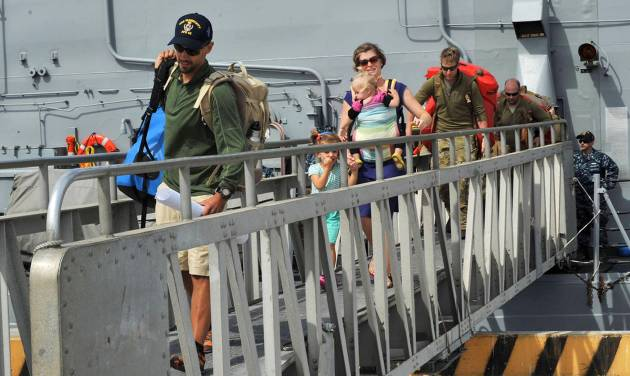 This photo provided by the U.S. Navy shows the Kaufman family disembarking from the USS Vandegrift on Wednesday, April 9, 2014, at Naval Air Station North Island in San Diego, following their rescue at sea on April 6.  Six days after the family of four found themselves helpless and adrift in a sailboat far into the Pacific with a vomiting and feverish 1-year-old aboard, a Navy warship delivered them safely to shore, where they had begun their attempted around-the world voyage before the child was born. (AP Photo/U.S. Navy)