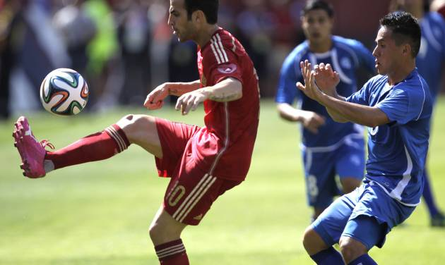 Spain's Cesc Fabregas, left, kicks the ball as El Salvador's Richard Menjivar, right, defends during the first half of an exhibition soccer game, Saturday, June 7, 2014, in Landover, Md. Spain won 2-0. (AP Photo/Luis M. Alvarez)