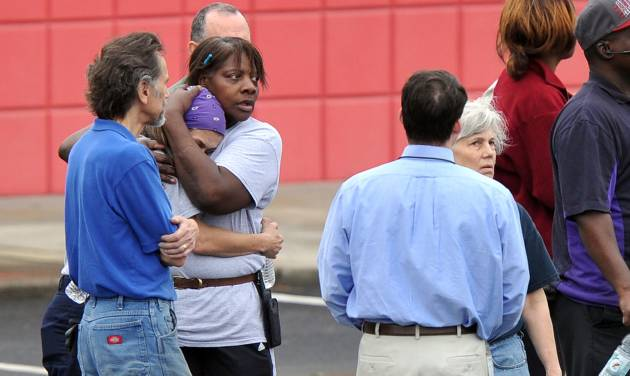 "FedEx Employee Lisa Aiken, wearing bandana, is embraced by a co-worker as other FedEx employees gather at a skating rink following a shooting at a FedEx facility in Kennesaw, Ga., on Tuesday, April 29, 2014.  A shooter described as being armed with an assault rifle and having bullets strapped across his chest opened fire Tuesday morning at a FedEx station outside Atlanta, wounding at least six people before police found the suspect dead from an apparent self-inflicted gunshot. ""He had bullets strapped across his chest like Rambo, a huge assault rifle and he had a knife,"" Aiken said.  (AP Photo/Atlanta Journal-Constitution, Brant Sanderlin)"