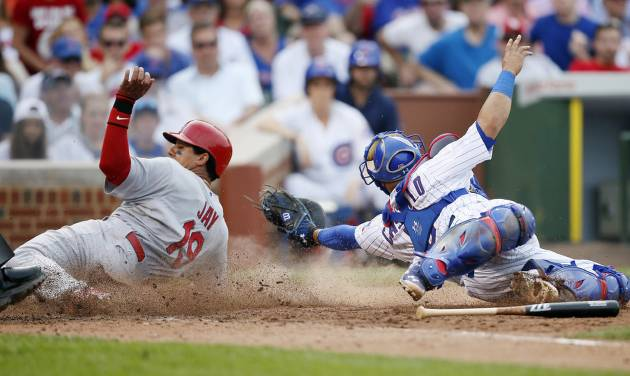 St. Louis Cardinals' Jon Jay, left, scores past Chicago Cubs catcher Welington Castillo during the seventh inning of a baseball game on Saturday, July 26, 2014, in Chicago. (AP Photo/Andrew A. Nelles)