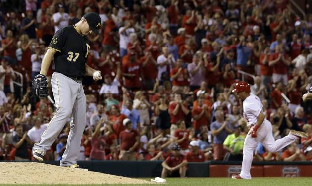 Pittsburgh Pirates relief pitcher Justin Wilson, left, stands on the mound as St. Louis Cardinals' Kolten Wong rounds the bases after hitting a solo home run during the seventh inning of a baseball game Wednesday, July 9, 2014, in St. Louis. (AP Photo/Jeff Roberson)