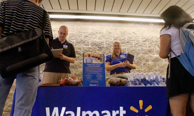 In this Thursday, Sept. 1, 2011, photo, Wal-Mart employees Jon Christians and Lori Harris take job applications and answers questions during a job fair at the University of Illinois Springfield campus in Springfield, Ill.  Wal-Mart Stores Inc., the world's largest retailer and nation's largest private employer, said Tuesday, Jan. 15, 2013, it is making a pledge to boost its sourcing from domestic suppliers and hire more than 100,000 veterans. The plans were to be announced as part of an address by Bill Simon, president and CEO of Wal-Mart's U.S. business, at an annual retail industry convention in New York. (AP Photo/Seth Perlman)
