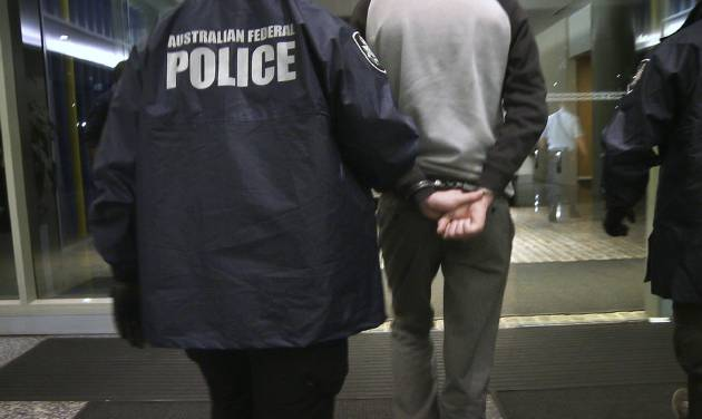 In this Tuesday, April 23, 2013 photo provided by the Australian Federal Police, a handcuffed man is escorted by police following his arrest on a charge of attacking and defacing a government website. The Australian man, who police say has claimed to be a high-level member of international hacking collective Lulz Security, was charged with two counts of unauthorized modification of data to cause impairment, and one count of unauthorized access to, or modification of, restricted data. (AP Photo/Australian Federal Police) EDITORIAL USE ONLY