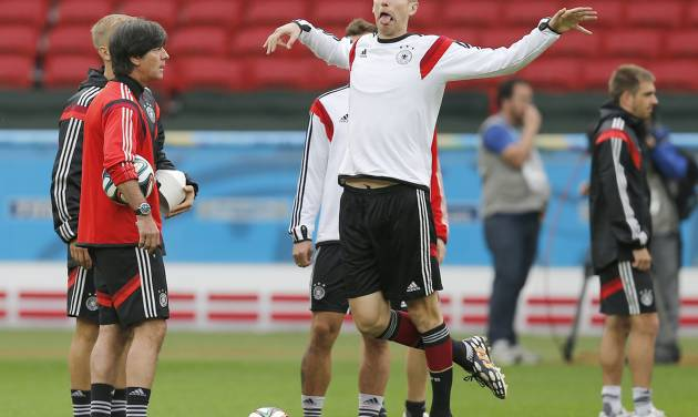 Germany's Per Mertesacker, center, grimaces to Germany's head coach Joachim Loew, left, during a training session at the Estadio Beira-Rio Stadium in Porto Alegre, Brazil, Sunday, June {try}, 2014.  Germany will play Algeria in a World Cup round of 16 soccer match on June 30. (AP Photo/Frank Augstein)