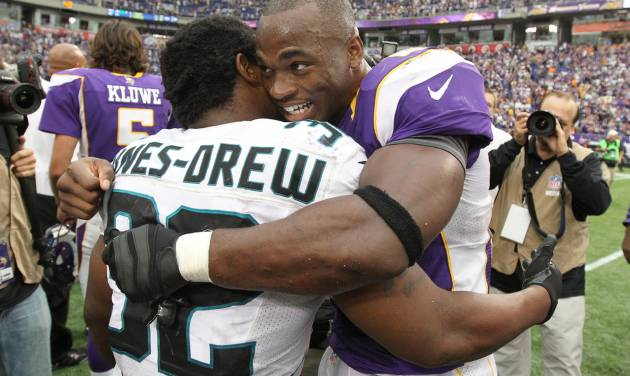 Minnesota Vikings running back Adrian Peterson, right, hugs Jacksonville Jaguars running back Maurice Jones-Drew after his team's 26-23 overtime victory in an NFL football game on Sunday, Sept. 9, 2012, in Minneapolis. (AP Photo/Genevieve Ross)