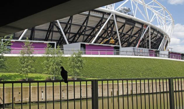 In this photo taken Wednesday June, 20, 2012, a bird sits on a railing overlooking the waterways, that were once polluted, at the bottom of the Olympic stadium, at the Olympic Park in London. After Sunday's closing ceremony it is hoped that once the massive crowds go home, bats will find themselves taking up residence in little bat boxes around the park, part of a lasting environmental legacy for east London's Olympic Park. (AP Photo/Elizabeth Dalziel)