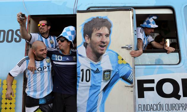 In this Saturday, June 14, 2014 photo, Argentine fans arrive in a bus decorated with a painting of soccer star Lionel Messi at the Copacabana beach in Rio de Janeiro, Brazil. Waving flags and banners, more than a thousand Argentine fans, many dressed in their team's traditional blue and white, crowded the Copacabana beachfront ahead of Argentina's World Cup match against Bosnia-Herzegovina Sunday in Rio's iconic Maracana stadium. (AP Photo/Leo Correa)